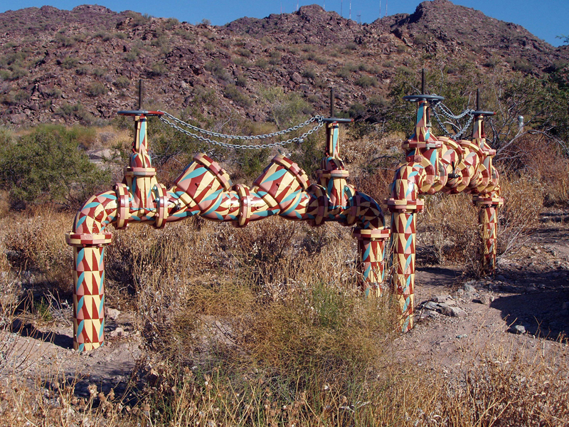 Photograph of Naturalized Infrastructure, a set of backflow devices painted with an unusual desert camouflage to match the natural color scheme
