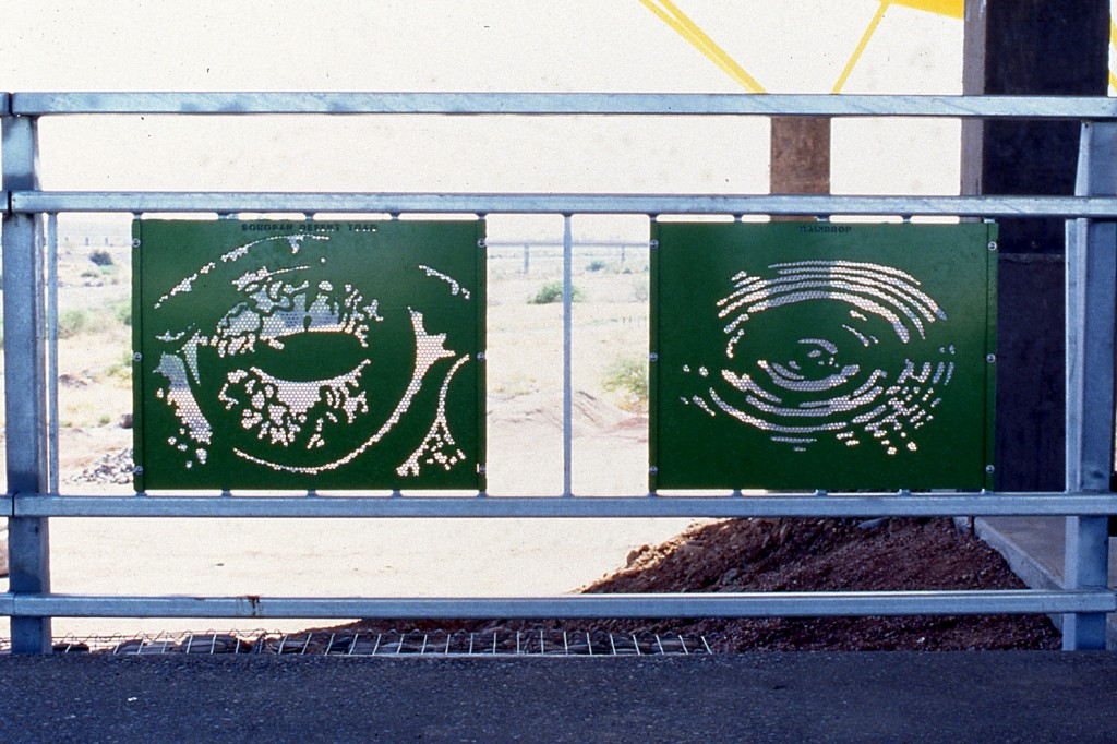 Photograph of cut and coated steel panels in railing at Rio Salado. The panels are bright green.