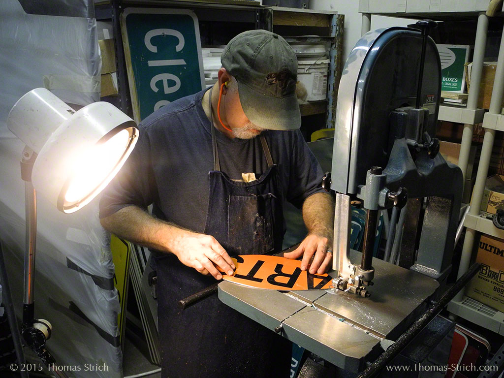 "Thomas Strich stands at a bandsaw, trimming a recycled street sign so that the text reads ""art"""